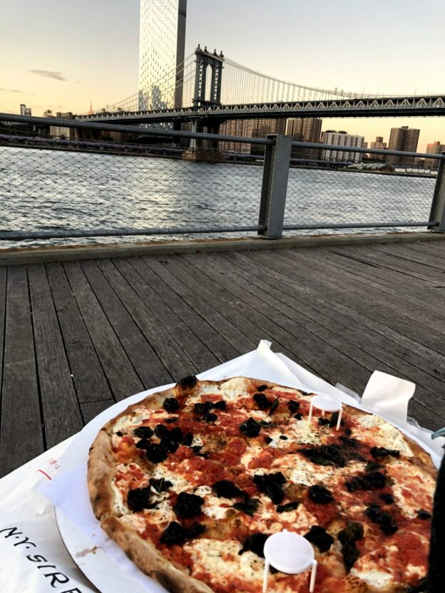 image of a large pizza margherita with olives. In the background, the Brooklyn Bridge at sunset.