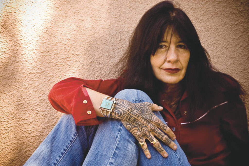 A photo of US Poet Laureate Joy Harjo. She is sitting against a wall and wrapping her right arm around her legs. She has long, brown hair and is wearing red lipstick. She is wearing a red shirt, blue jeans, a bracelet, and her right hand is entirely decorated with Native American tattoos.